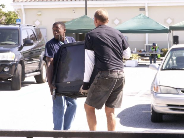 "Cory Lewis carries a television Saturday toward his car, where his wife and three of their five children await, with the help of Junk in the Trunk volunteer Wolfgang Deininger. ""I can't afford to buy one for the kids right now,"" Lewis said. ""Hopefully, it works."""