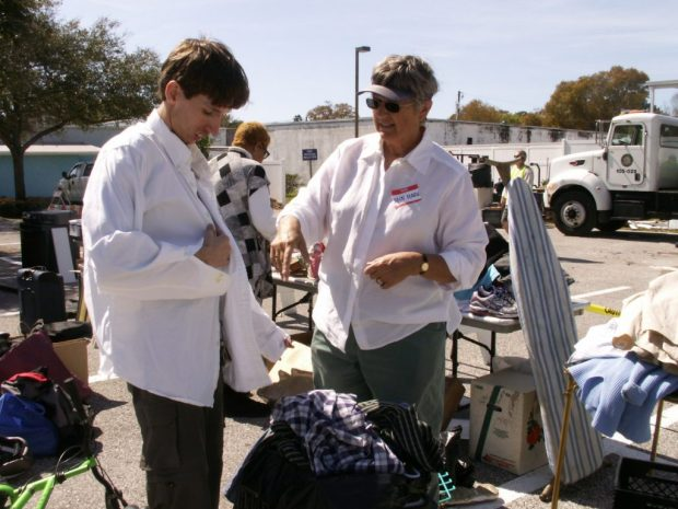 "Louis McClanahan tries on a shirt chosen by volunteer Ann Marie Anderson from a bag of clothing donated at Saturday's Junk in the Trunk at the Gulfport Neighborhood Center. McClanahan said he has picked up computers and other stuff at previous Junk in the Trunk events. ""I reuse it,'' he said. ""Try to get it to work again."""