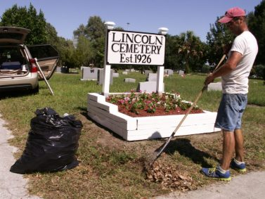 Scott Hollman of St. Petersburg cleans up after installing a new sign and planting fresh flowers at the entrance of Lincoln Cemetery on 58th St. S. on May 7.