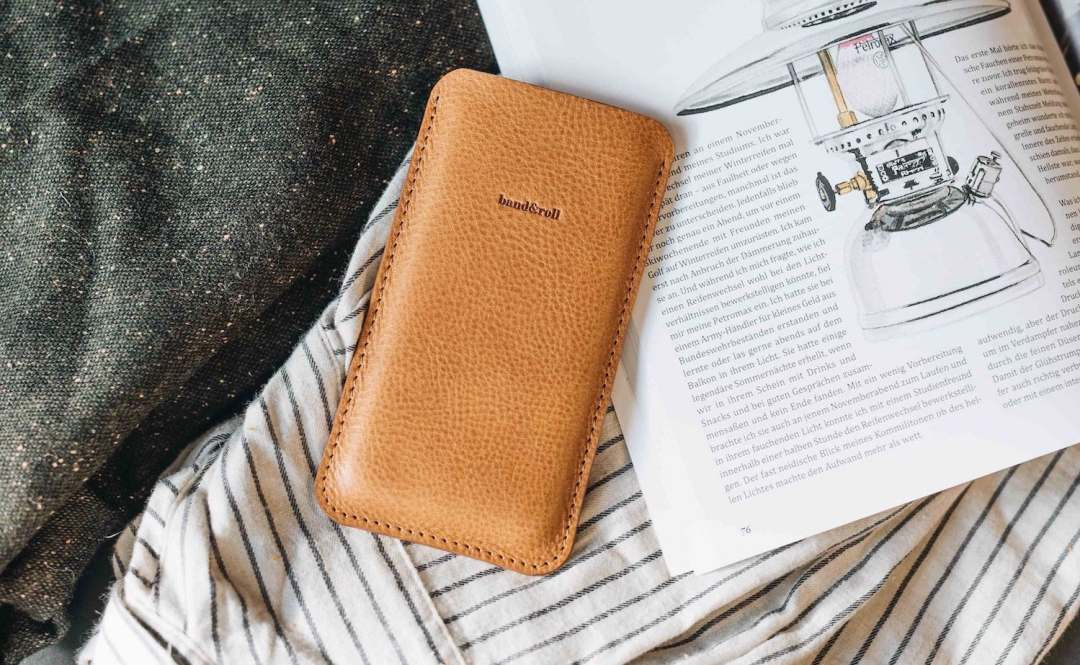 The leather phone sleeve is on a book and striped fabric.