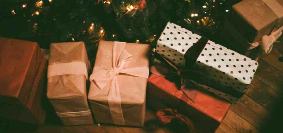 assorted gift boxes on floor near christmas tree