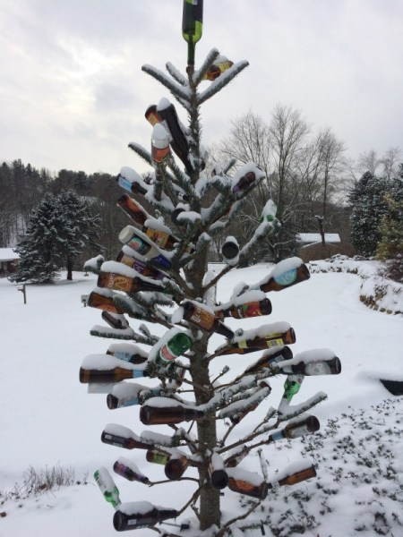 A repurposed Christmas tree set up as a bottle tree