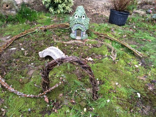 Creating a mossy fairy garden by transplanting patches of moss and pressing them into the soil and saturating with water