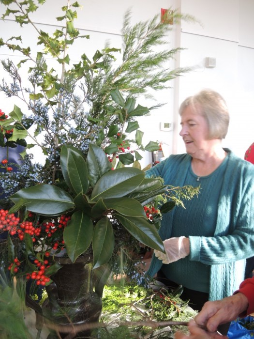 Using fresh cut greens, a volunteer puts together a large arrangement in a towering urn