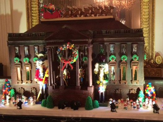 Nutcrackers flank the door of the dark chocolate gingerbread house