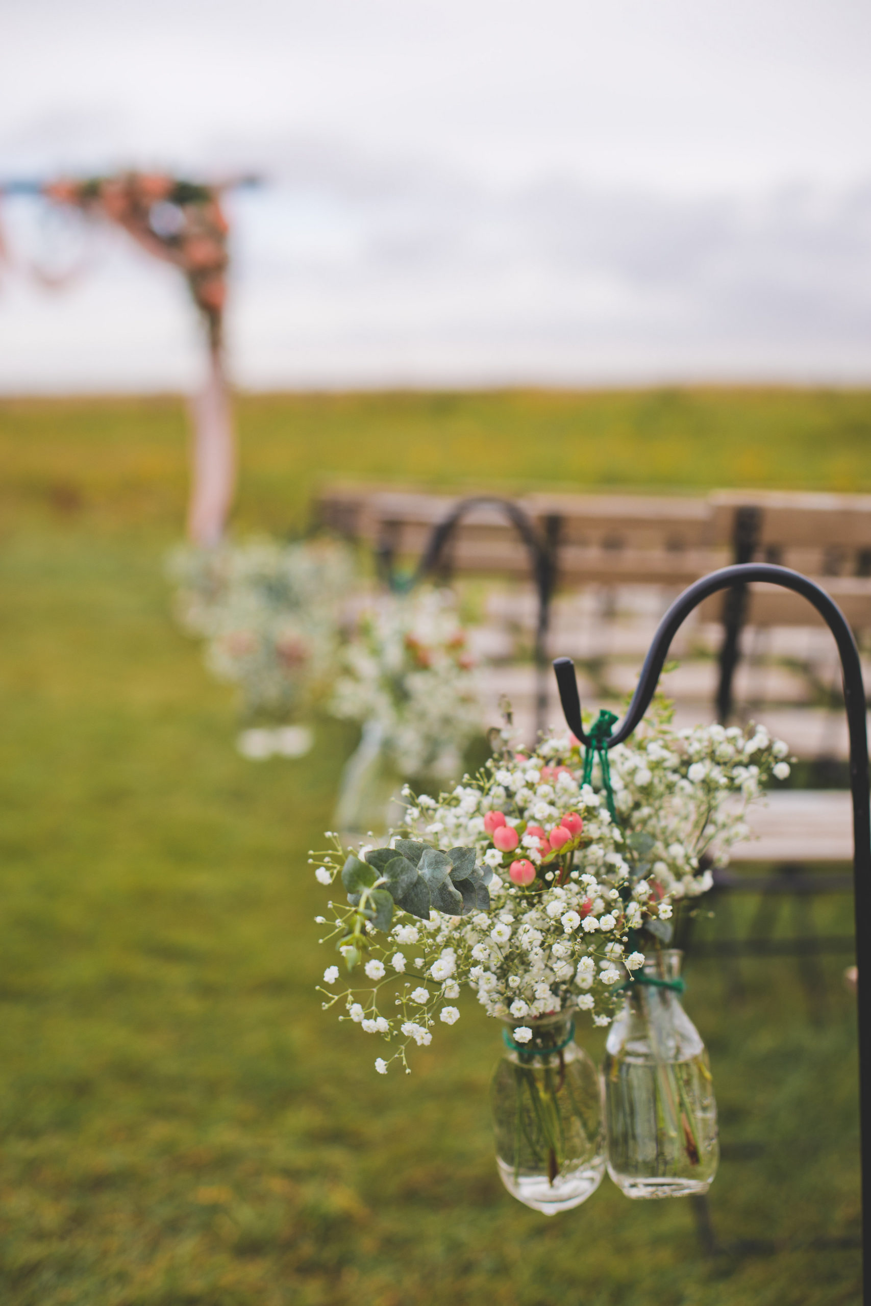 wedding aisle with shepherds hooks and hanging jars with white babies breath and pops of pink in a prairie wedding ceremony space in Alberta, Canada- The Gathered