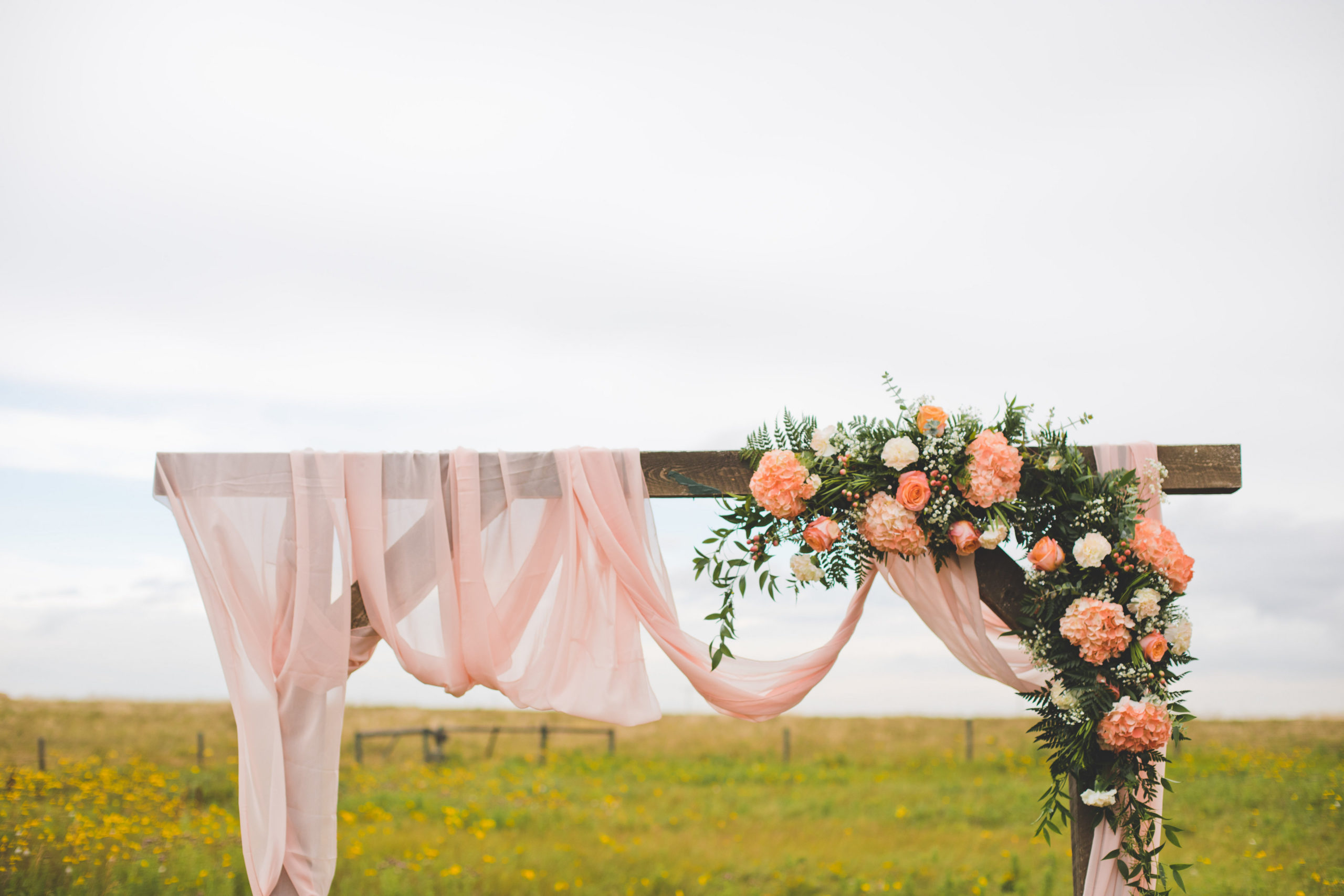 Wood Arbor in a prairie field decorated with pink chiffon and vibrant pink, coral and peach toned flowers. The Gathered, Calgary, Alberta