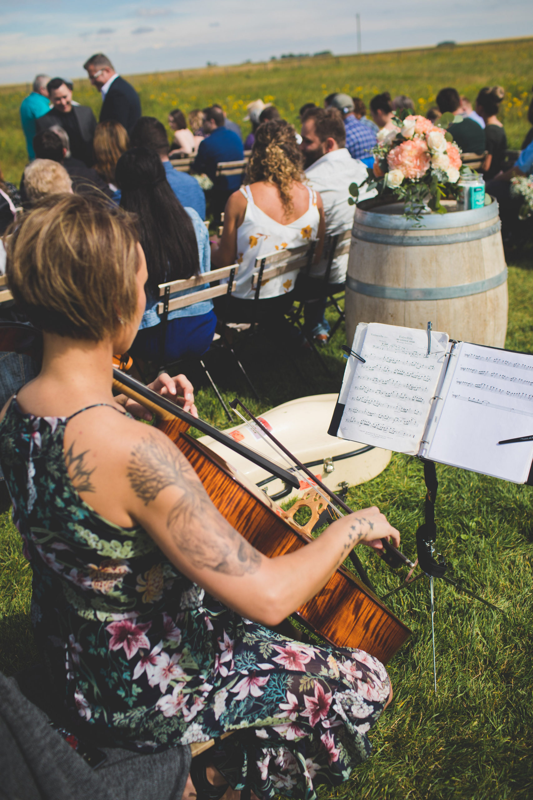 Violinist playing at an outdoor ceremony in a prairie field in Calgary, Alberta.