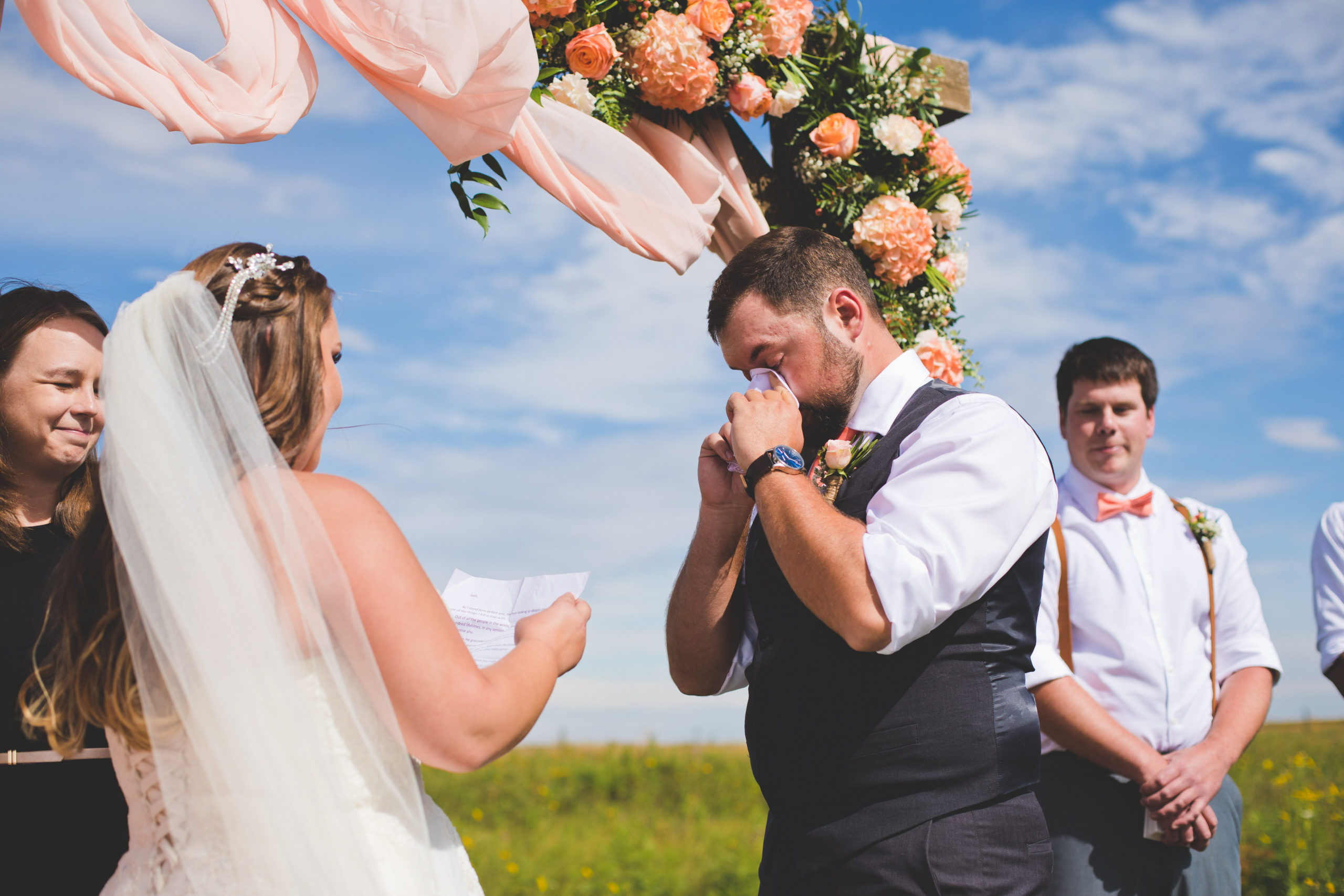 bride and groom exchanging vows under their peach and coral decorated arbor in Alberta, Canada