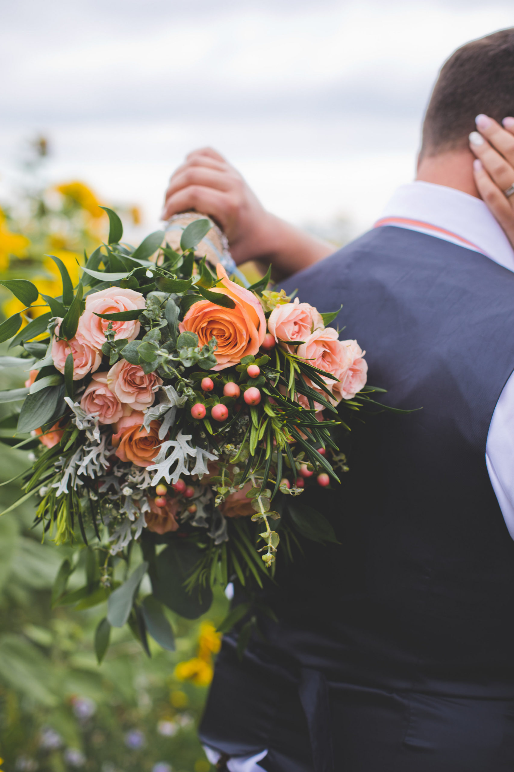 coral and peach toned flower bouquets add a vibrant flair to this outdoor prairie wedding on a rainy day in Alberta, Canada.