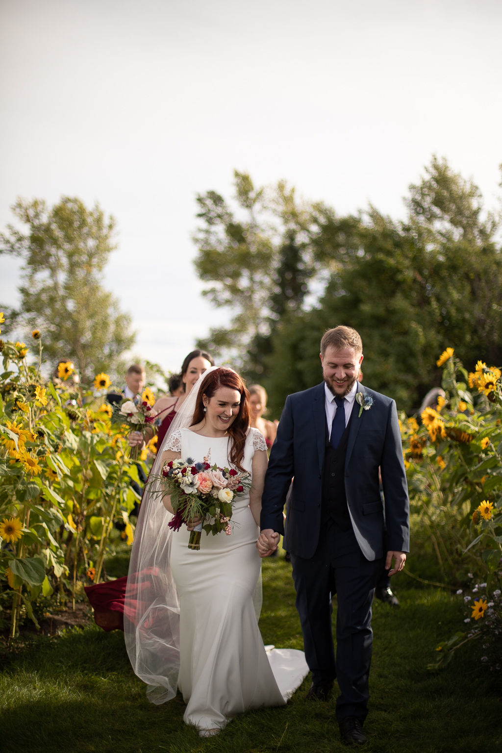 bride and groom walk down a grassy path surrounded by yellow sunflowers! www.thegathered.ca