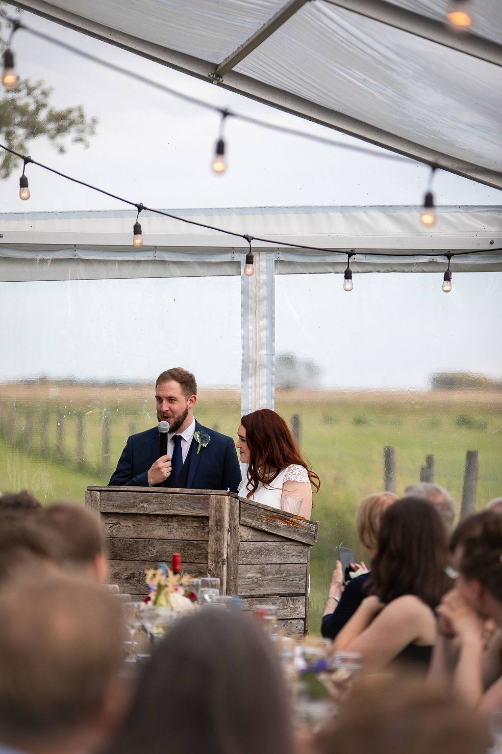 a bride and groom give a speech at their clear tent venue at the Gathered in Calgary, Alberta. www.thegathered.ca