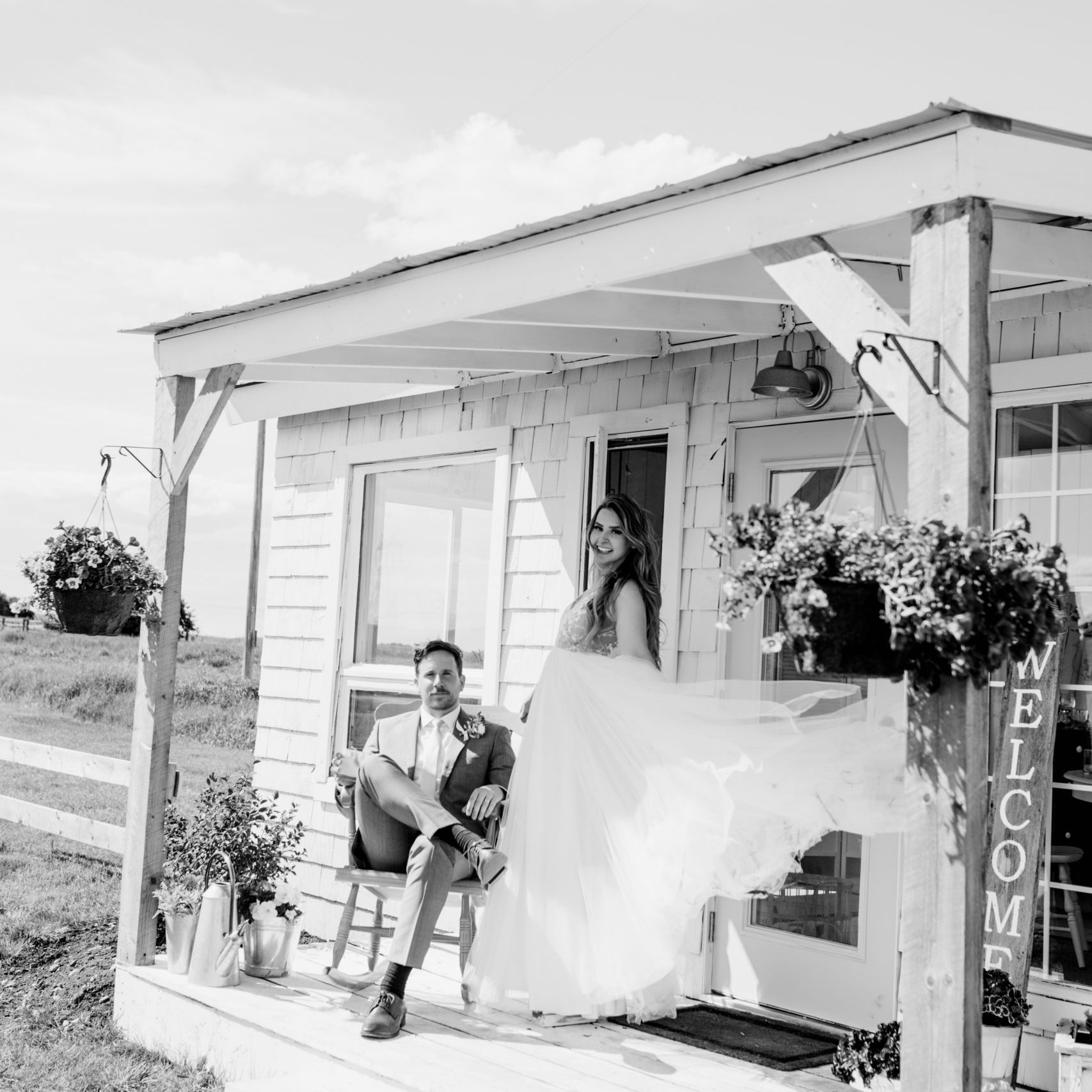 black and white image of a little cottage, groom sits on a rocking chair while bride stands beside him her dress blowing in the wind. www.thegathered.ca