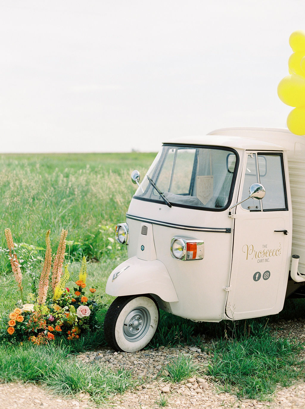 bright colored floral arrangement sit in front of a cream colored prosecco cart