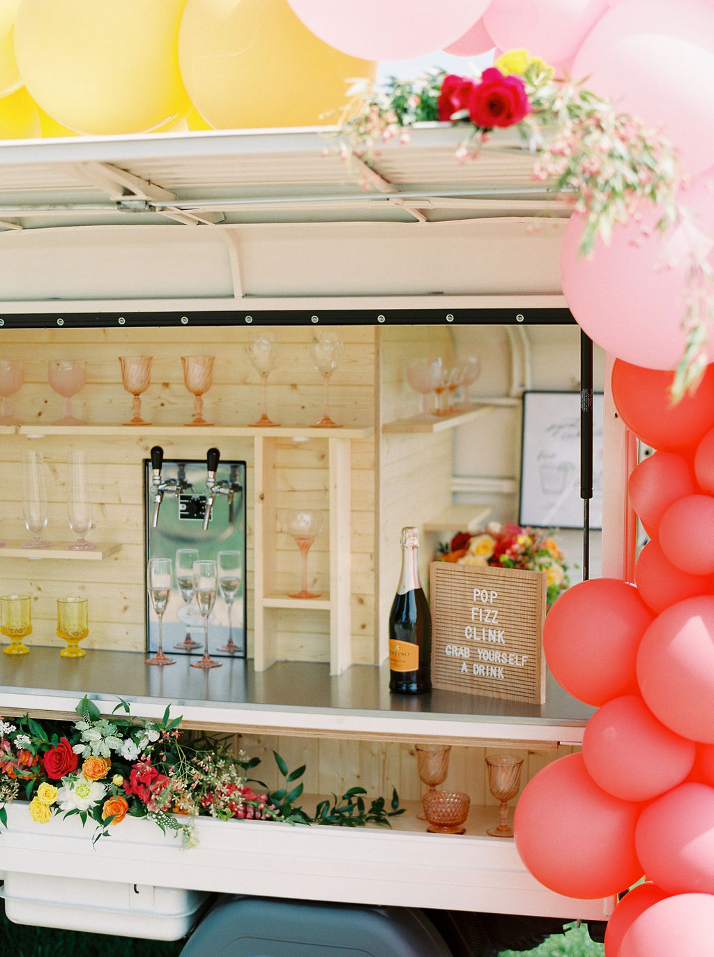 bright colored tones of flowers and balloons decorate a small wine cart