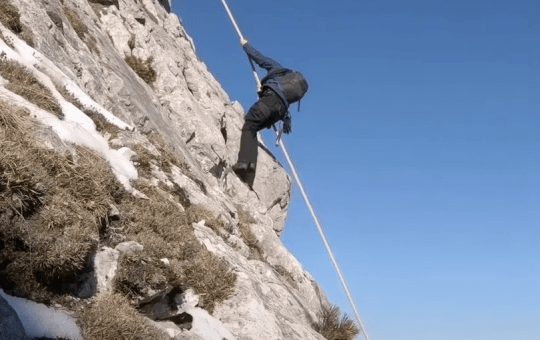 Bear Grylls uses a rope to climb down a gorgeous mountain slope. (Image: National Geographic)