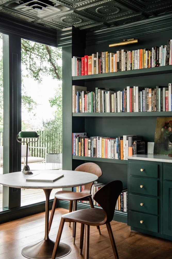 Bespoke green library with round table and mid-century like chairs