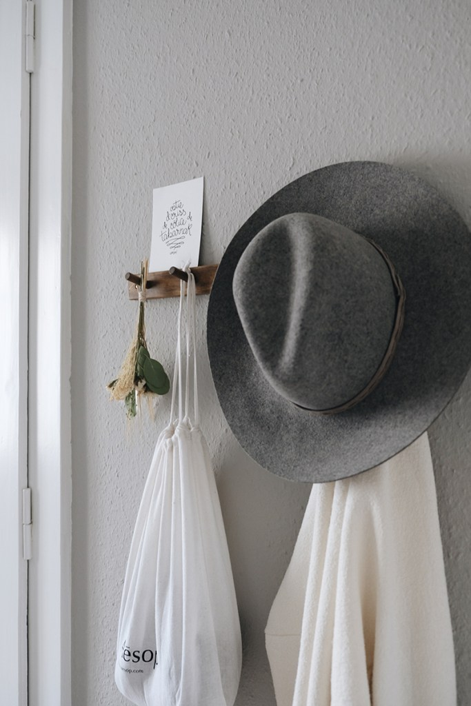 a hat on a peg rail with dried bouquet