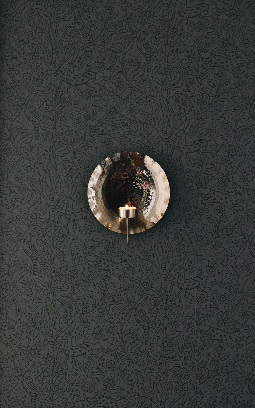 H&M home brass candle sconce on dark green wallpaper