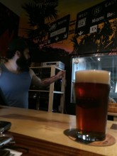 David Rodriguez at work, under Kunde's mural at the Wynwood Brewing Co. Tap Room.