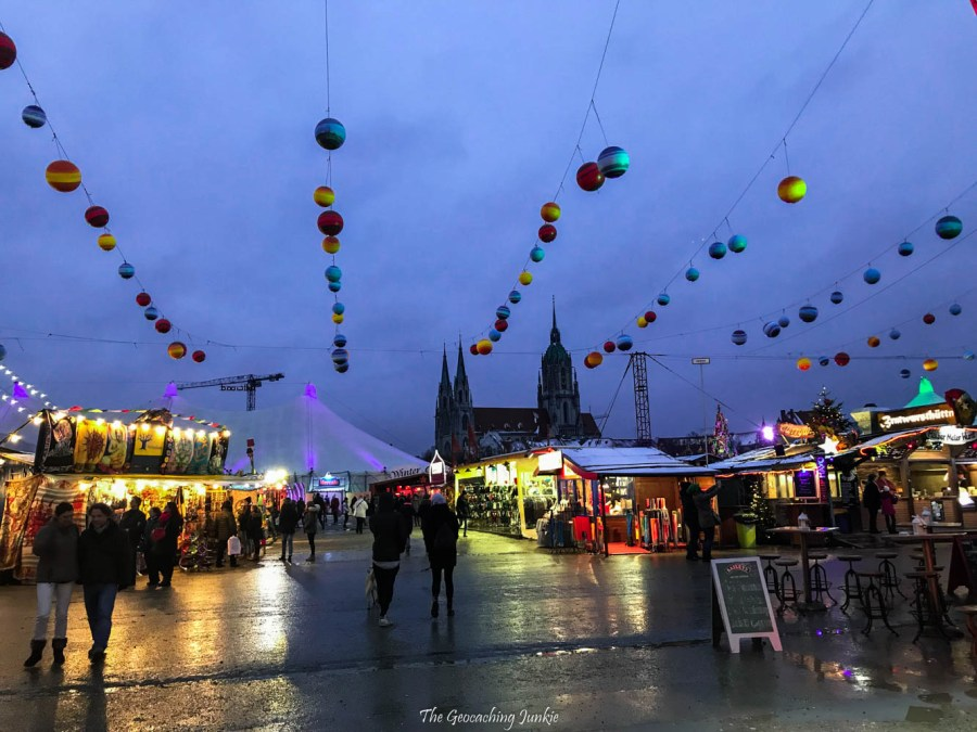 A Christmas scene at Winter Tollwood in Munich, Germany with strings of baubles high above, and Christmas huts and tents in the background