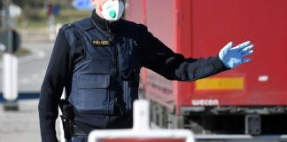 A German police officer stops a driver at the border crossing between Austria and Germany.