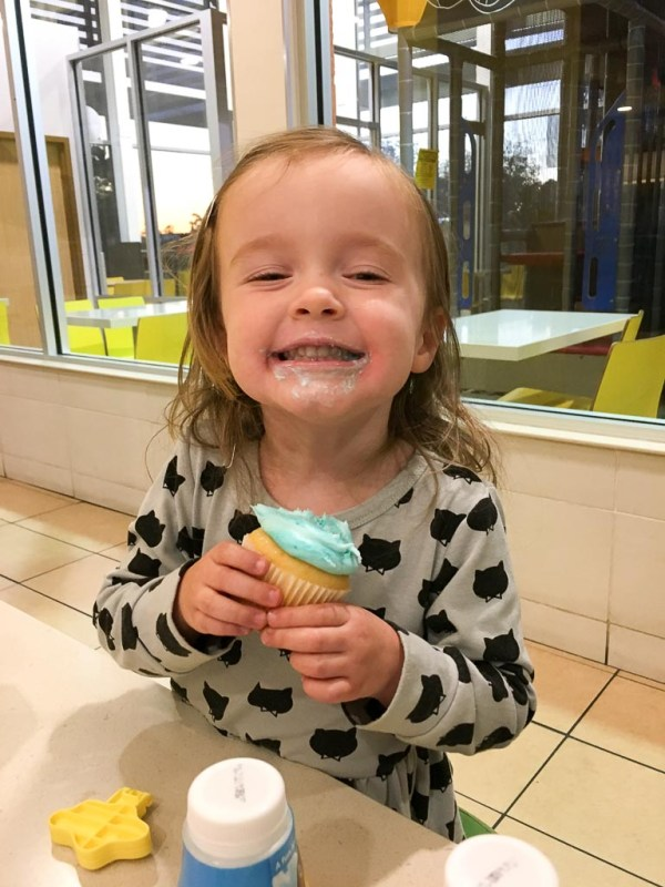 little girl with cupcake and messy face