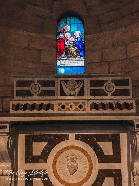 A side altar that has a stained glass of an older St. Joseph being cared for by the Virgin Mary and Jesus