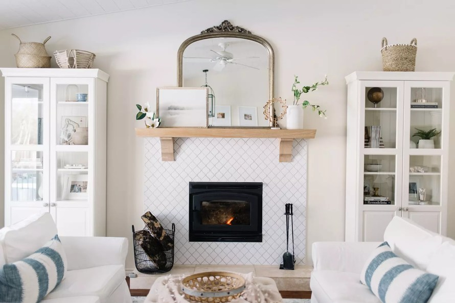 A styled fireplace mantle flanked by a pair of glass doored bookshelves