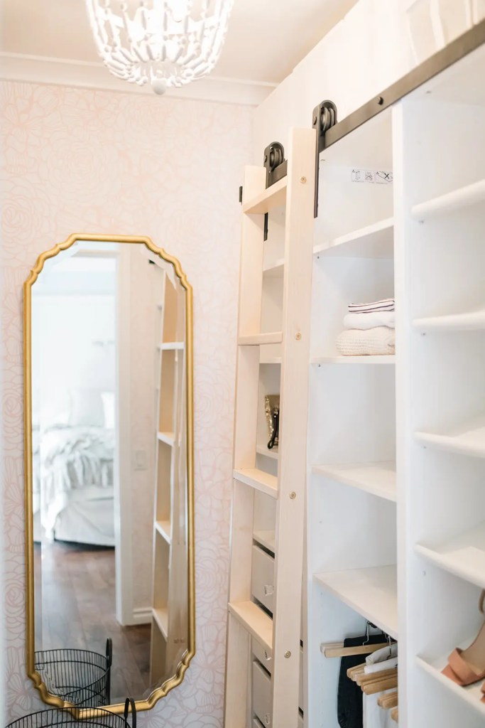 A mirror and rolling ladder in a custom closet