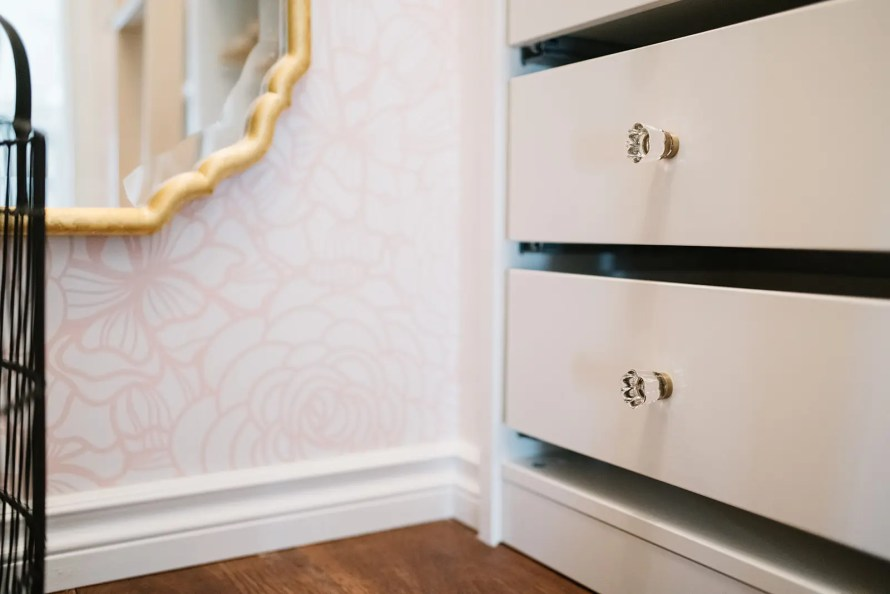 Closet drawers and pretty wallapaper in a custom closet