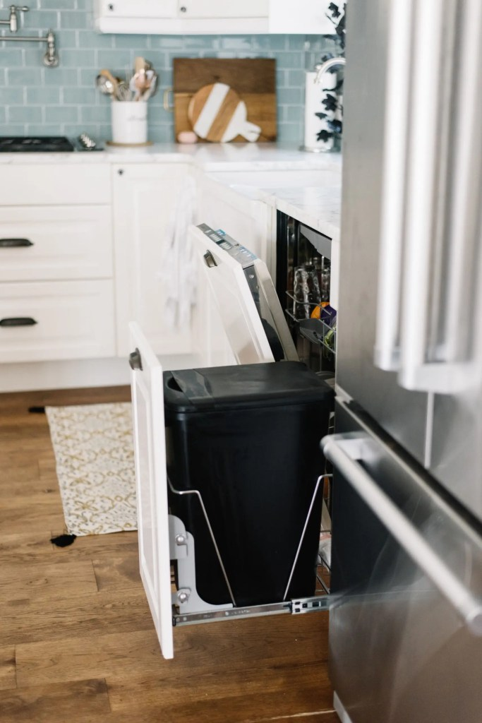 dishwasher and garbage pullout are hidden behind cabinetry panels