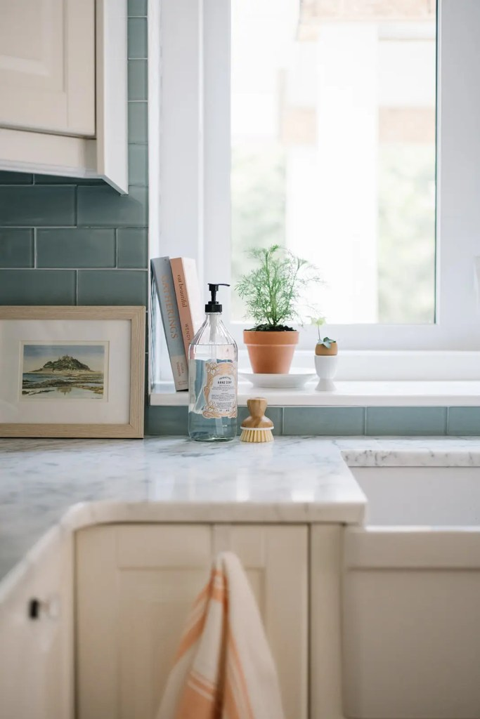 A collection of books, soap and veggie brushes make the kitchen feel pretty in the summer