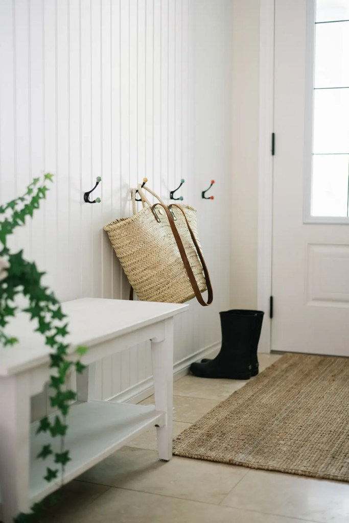 The entryway is simplified for summer with a French market basket and some gardening boots
