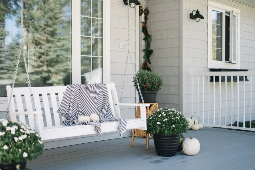 Front porch with white porch swing, grey shingles, white railing and fall decor