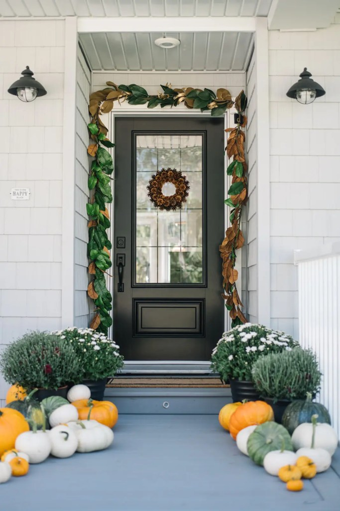 Black front door decorated for fall with magnolia garland and pine cone wreath.