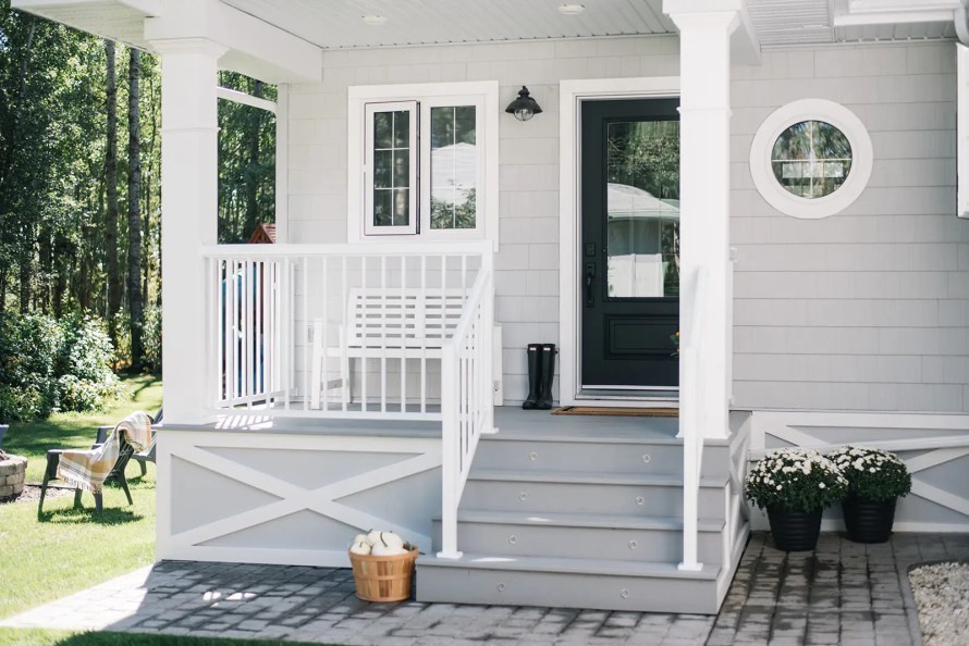 A modern farmhouse style front porch with grey decking and shingles and a black door.