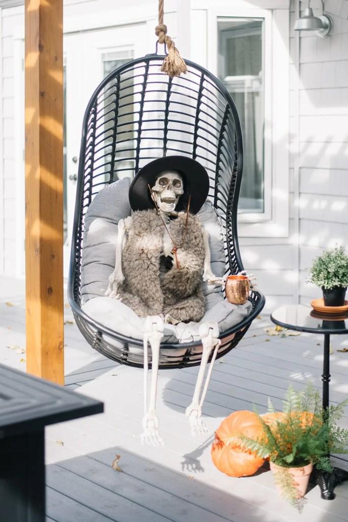 Halloween skeleton decoration sitting in an outdoor swing