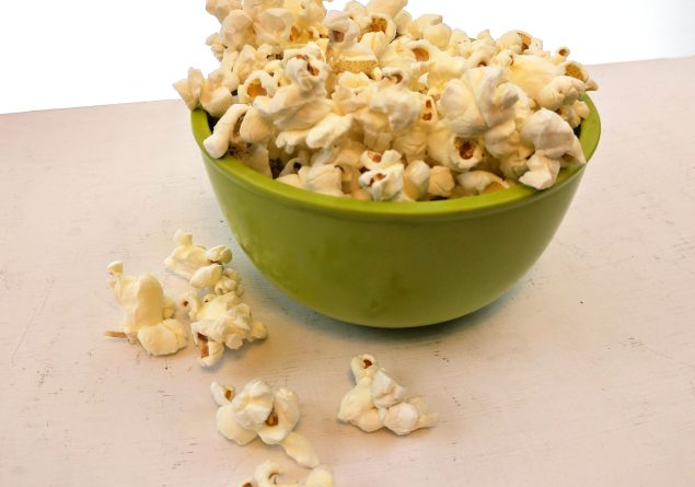 popcorn in a green bowl on a white table