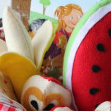 felt food: banana, apple piece, watermelon slice tucked in a basket with board game