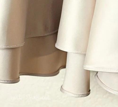 bottom hem of a beige satin dress with rolled hem