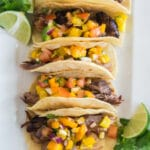 overhead view of crockpot carnitas in tacos with mango salsa on a white plate, lime and cilantro garnish