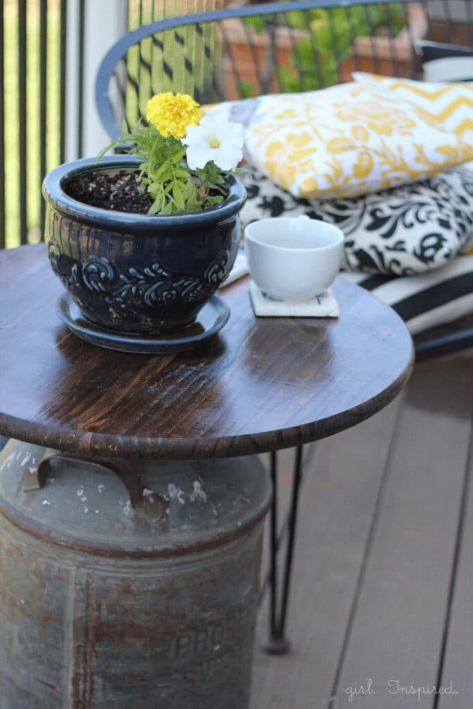 Wooden top outdoor side table with antique milk can base, blue pot of flowers and white mug on table, black bench with yellow and black throw pillows