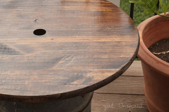 stained and sealed round wooden side table top with hole drilled in center