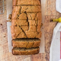 sliced banana nut bread loaf next to cooling rack, with banana peel and tea towel