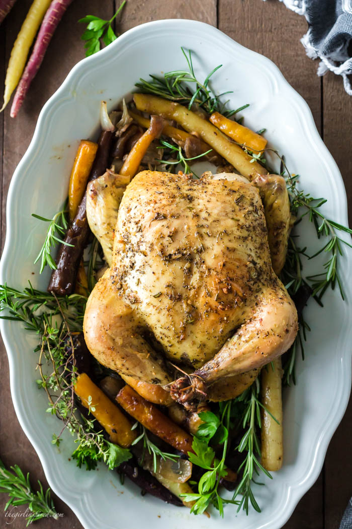 whole roasted chicken on white platter with rainbow carrots and fresh herbs