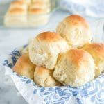 dinner rolls stacked in a bread basket with white and blue floral linen, baking dish with rolls