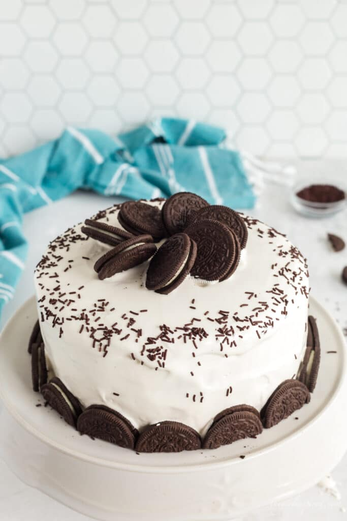 Oreos on top of ice cream cake and half oreos around bottom border with white frosting and chocolate sprinkles on white plate with aqua linen