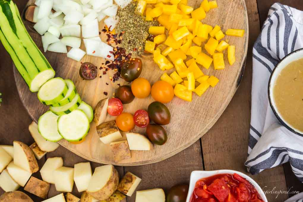 colorful veggies chopped on a cutting board including onions, bell pepper, zucchini, potato, and tomatoes