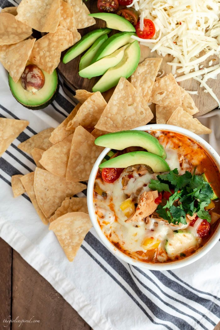 white soup bowl with cheese, avocado, and cilantro-topped soup, tortilla chips, and grated cheese on a striped dish towel
